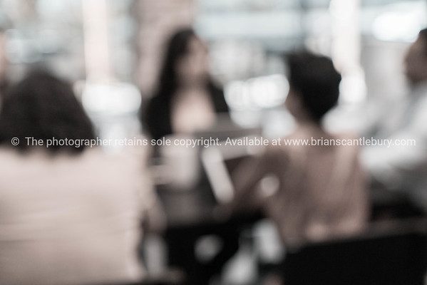 Business meeting effect desaturated and out of focus with group diverse women and men sitting around table discussing a business plan.