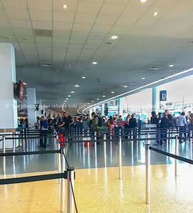 People in distance in airport queueing for tickets