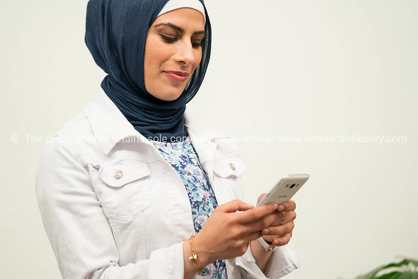 Islamic woman using mobile phone on white background.