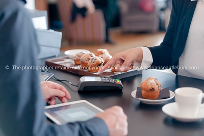 Making contactless payment in cafe with mobile phone.