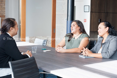 Three Maori women on one side of table in business meeting