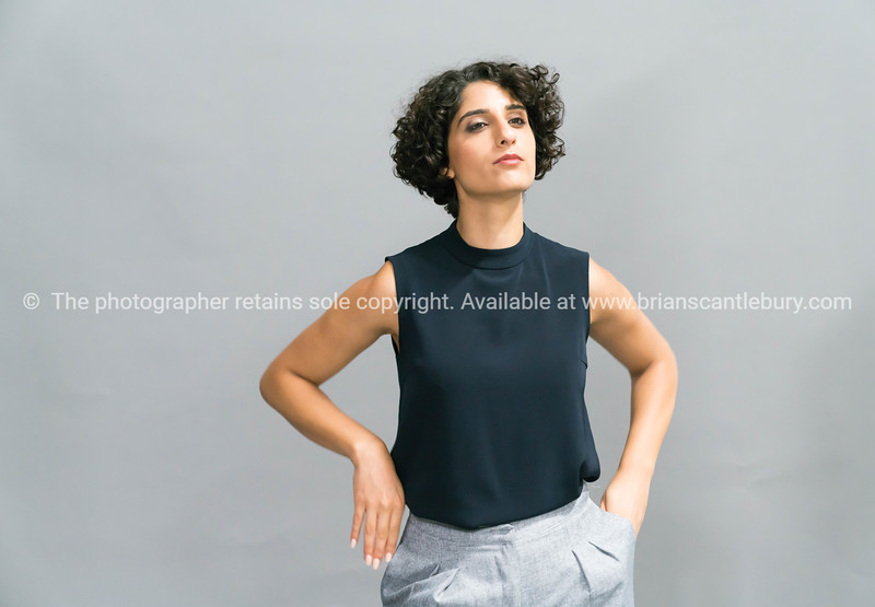 Smartly dressed business woman of middle eastern heritage standing holding tablet device