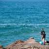 """Rock fishing. Fishermen stand on rocks at base of the Mount fishing.<br /> <br /> Model Release; No. For personal or editorial use. See;  <a href=""""http://www.blurb.com/b/3811392-tauranga"""">http://www.blurb.com/b/3811392-tauranga</a>"""