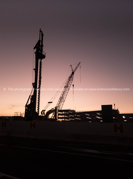 Construction equipment silhouetted against evening sky.