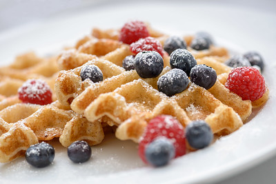 Close up of a blueberry and raspberry topped waffles