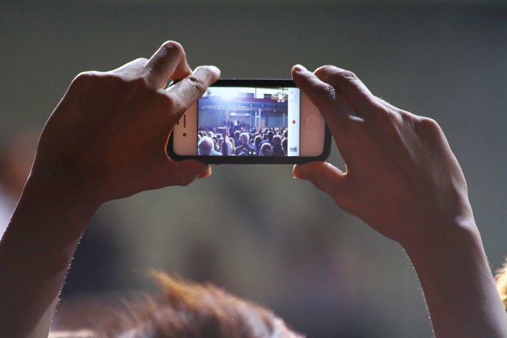 Iowa City, IA- A participant take a video when President Obama speaks on student debt at the Field House on April 25, 2012. (SOT Photography)