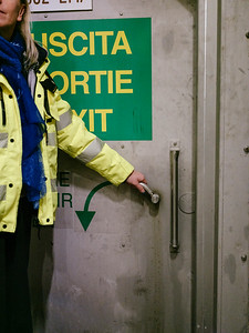 Erika Noro (communication service) opening the door to the evacuation tunnel, from emergency shelter number 17 - Samuel Zeller for the New York Times
