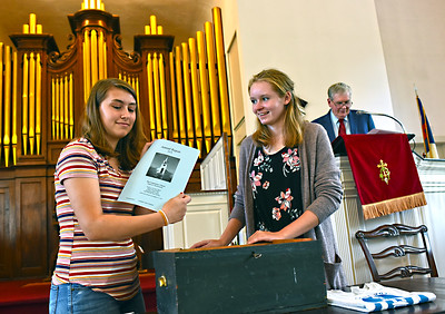 Showing items that are being repacked back into the time capsule to be reopened in 25 years, L-R, Grace Audette 16 of Ayer and Jessie Nadeau 15 of Pepperell, in back is Marle Green Co-Chairman of the 100th Anniversary Commemoration Committee. SUN/David H. Brow
