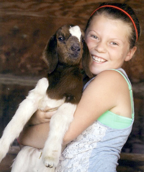 Jordyn Sailer poses for a photo holding her goat, Lily, in the summer of 2015. Jordyn died in June of this year after battling leukemia. Her family sold her pig, Favorite, at the Larimer County Fair Junior Livestock Sale during the Larimer County Fair Wednesday. (Photo submitted by Sailer family)
