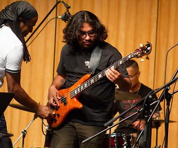 Doug Wimbish helps student Jack Ocampo with playing Doug's personal bass.