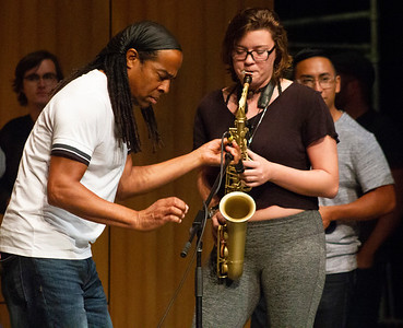 Doug adjusts the microphone for saxophone player Abby Wilson.