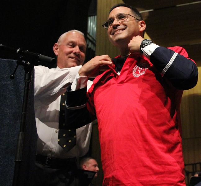 Dick Taylor helps Captain Quinones don a BC veterans services shirt.