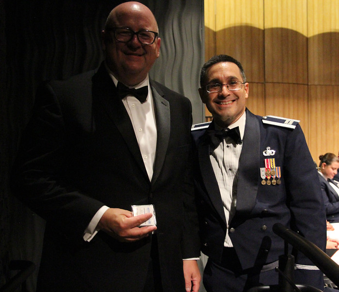 Captain Quinones presenting a special commemorative coin to Michael Stone