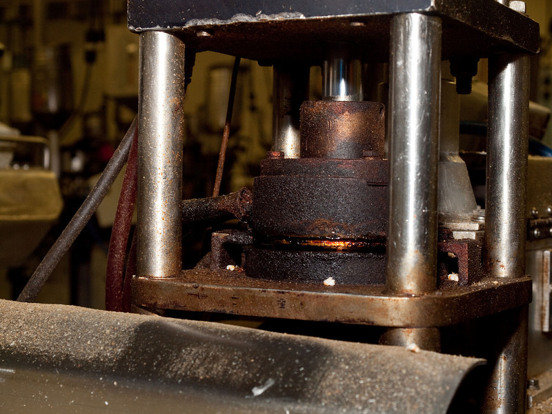 A close-up of one of the rice cake makers.  The round, brown-caked die has been automagically loaded with rice grains and a hydraulic ram (the shiny arm is visible above the die) has closed the die, where pressure and heat are being applied.  100811_3154
