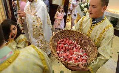 Bob Donaldson/Post-Gazette. 20150412. Orthodox Easter. Standalone. Local. Acolyte NAME carries Easter eggs dyed red for distribution following the Paschal Vespers service Easter morning Holy Trinity Greek Orthodox Church in McCandless. The eggs are dyed red to symbolize the blood of Christ. Because Orthodox churches follow the Julian calendar, their Easter falls week after most Christian denominations. Writer: Standalone. Story Slug: unknown