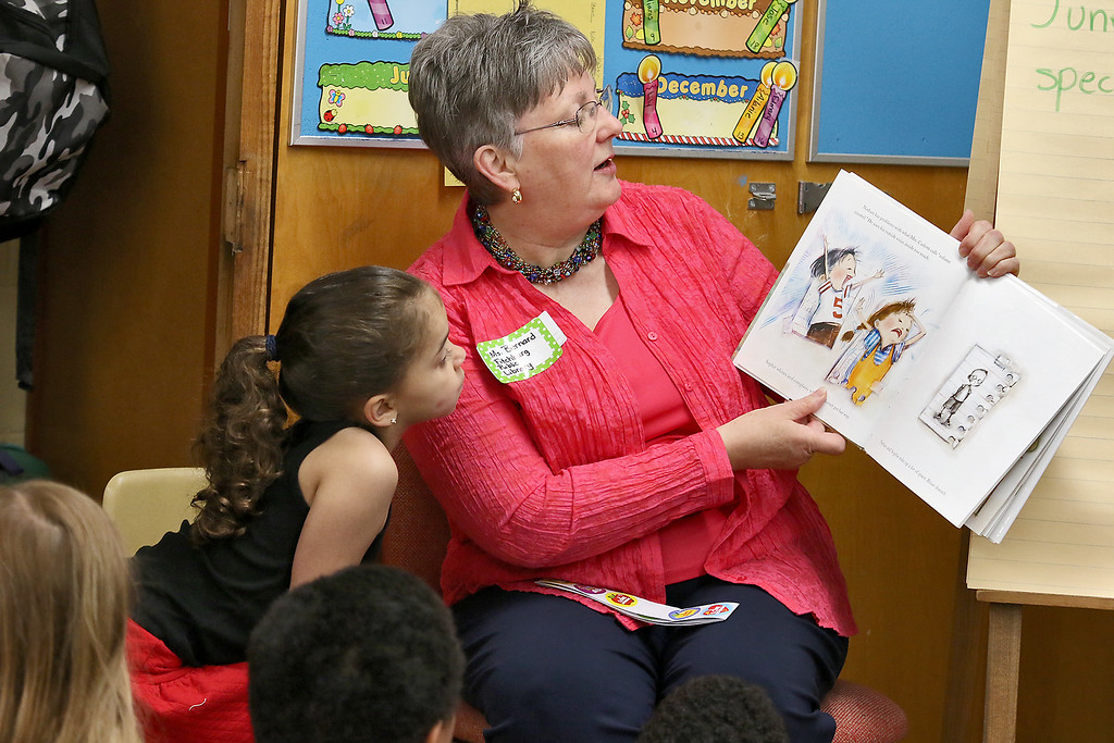 . Reingold Elementary School Community Reader Day was held on Thursday, June 15, 2017. First grader Edmary Perez Vazquez tries to get a close look at the pages of the book that Sharon Bernard of the Fitchburg Public Library was reading to Laura Champas\'s class during community reading day at the school. SUN/JOHN LOVE