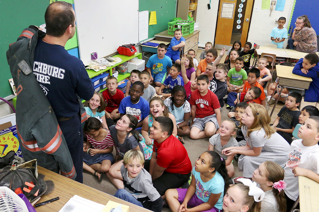 . Reingold Elementary School Community Reader Day was held on Thursday, June 15, 2017. Fire Lt. Dante Suarez talks to the third grade students in Brenda Suarez and Blair Carroll\'s classes about his gear after reading to them. SUN/JOHN LOVE