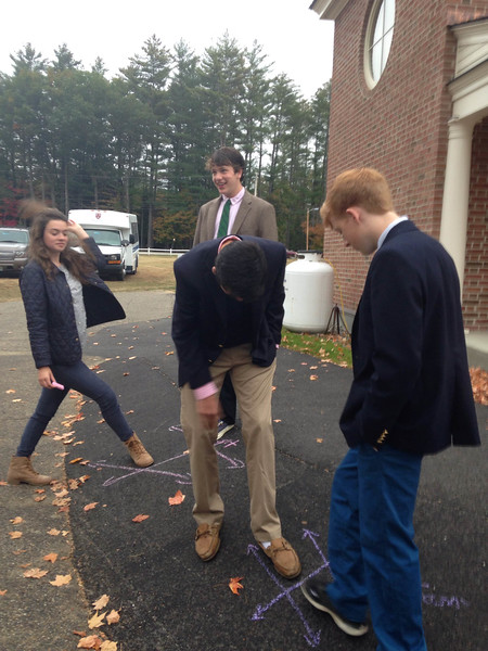On Tuesday morning, Mr. Cirone and his Geometry class spent some time outside in the parking lot with sidewalk chalk. They were braving the rain in order to practice some properties of angles. Each group drew two lines that were cut by a transversal and were then stepping into their drawings to demonstrate different pairs of angles. It looked like fun! Pictured here are Mary Nunges, Stuart Clifford, Morgan Dawkins, and James Sullivan.