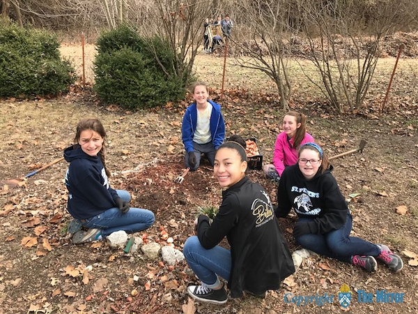 BULB PLANTING—A few ​seventh grade girls plant​ed​ tulip bulbs in the Prayer Garden​ at Sacred Heart Parish, Webb City. (<i>The Mirror</i>)