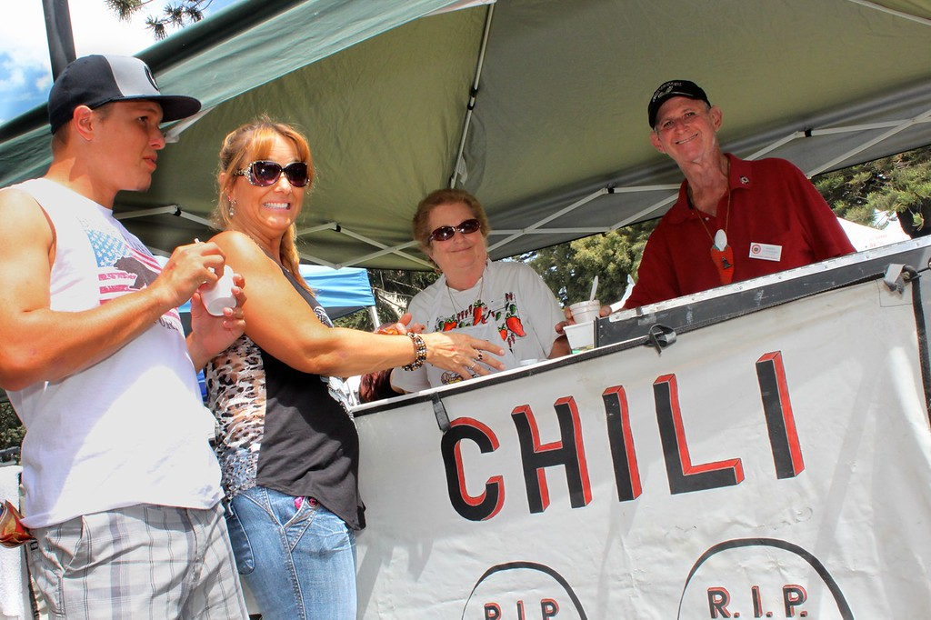"""Jacob and Missy Atwater of Camarillo try a taste of """"R.I.P. Chili"""" served up by Sylvia and Barry Steinberg of Woodland Hills.  The chili's slogan; """"everybody's dying for a bowl""""."""