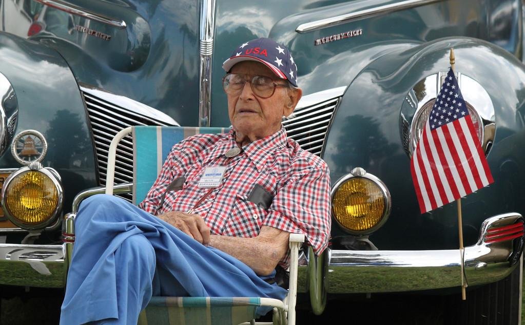 Win Burkhardt of Camarillo rests his eyes as passersby admire his 1939 Mercury sedan.