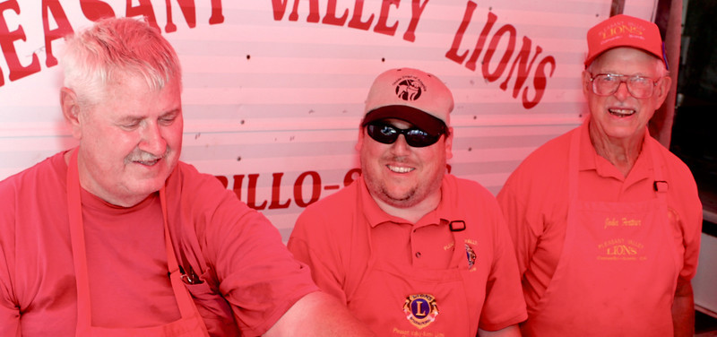 "Looking just a bit devilish under their red canvas awning, Camarillo/Somis Pleasant Valley Lions Club members live up to their nickname, ""The Big Red One"".<br /> From left, John Knittle, Club President Greg Steinmetz  and John Fortner flipped Lion Burgers, spread general cheer, and continued the club's 67-year tradition of raising funds for Camarillo and Somis causes.<br /> In addition to supporting the Camarillo Hospice Tree of Life, the Lions also sponsor scholarships at Rio Mesa and Camarillo High Schools, provide eye exams, glasses and school clothes for local youths and throw a bang-up fireworks show every Fourth of July."