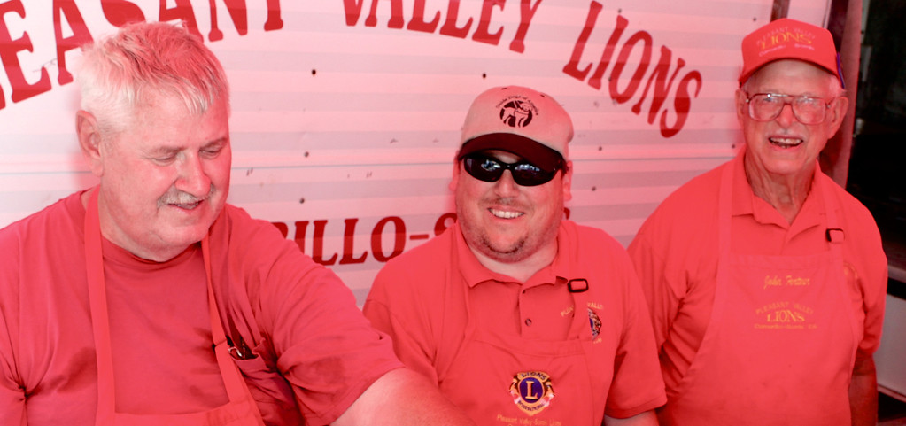 """Looking just a bit devilish under their red canvas awning, Camarillo/Somis Pleasant Valley Lions Club members live up to their nickname, """"The Big Red One"""".<br /> From left, John Knittle, Club President Greg Steinmetz  and John Fortner flipped Lion Burgers, spread general cheer, and continued the club's 67-year tradition of raising funds for Camarillo and Somis causes.<br /> In addition to supporting the Camarillo Hospice Tree of Life, the Lions also sponsor scholarships at Rio Mesa and Camarillo High Schools, provide eye exams, glasses and school clothes for local youths and throw a bang-up fireworks show every Fourth of July."""