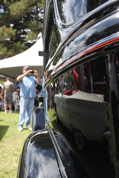 Neil McCarthy grabs a snapshot of Ken and Donna Kraft's pristine 1933 Ford Tudor sedan with his camera phone.<br /> Reflected in the Cal Custom black single-stage paint job is another Ford; a cream-colored 1955 Thunderbird convertible.