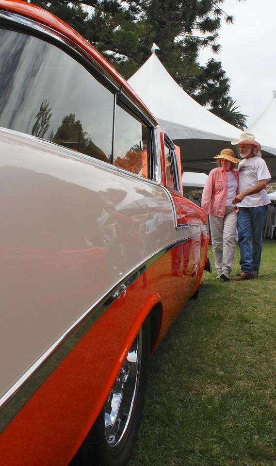 Karen Bates and DuWayne Weatherman of San BuenaVentura cast their gaze on the sleek lines of a 19xx Chevrolet Station Wagon in Creamsicle colors of ecru and orange.