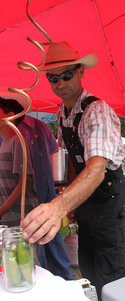 "Cliff Ashlock, left, and Shane Theissen did a brisk business with their ""Hillbilly Chili"" at the fifth Annual Camarillo Chili Cook-Off and Country Music Festival.<br /> Asked if costuming and booth decor was a factor in the voting, Theissen adjusted the copper coil to his faux ""chili still"" and remarked, ""It couldn't hurt""."