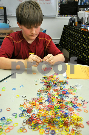 -Messenger photo by Joe Sutter<br /> <br /> Corbin Dutcher, sixth grade, ties rubber bands together to make a bracelet which will be sent to Cambodia to young women rescued from human trafficking.