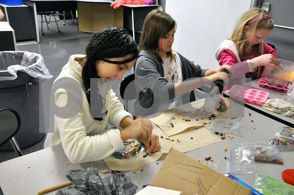 -Messenger photo by Joe Sutter<br /> <br /> Sophia Calderon, fifth grade, pounds old crayons to pieces, along with Hannah Sampson, fifth grade, and Megan Gilbert, sixth grade. The crayons are then melted, poured into molds, and put into care packages sent to orphanages in Haiti.
