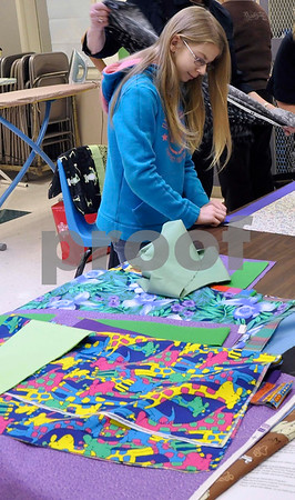 -Messenger photo by Joe Sutter<br /> <br /> Sixth-grader Brianna Ell helps volunteers Marilyn Jensen and Heather Nicholls measure out the pieces of colorful fabric and pin them in place so other students can sew them into pillowcases.