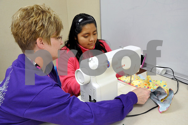 -Messenger photo by Joe Sutter<br /> <br /> Vicki Parrott helps sixth-grader Yenci Calles sew up a colorful pillowcase. The pillowcases were one of Aaron Eilerts' well-known projects. He used to buy the fabric himself and create the cases for children at the local hospital. Calles said she's never really sewed before.