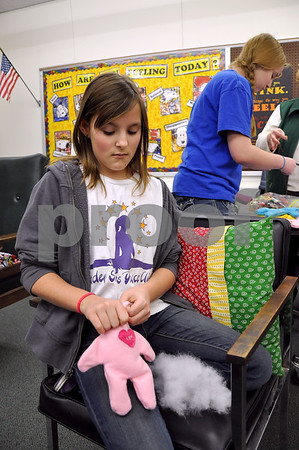-Messenger photo by Joe Sutter<br /> <br /> Hannah Sampson, fifth grade, pushes stuffing into a homemade doll created by freshman Sarah Wilson. The dolls will be sent to orphans in Haiti, and are one of the ways Aaron Eilerts Day is now reaching kids around the world, not just in Iowa.