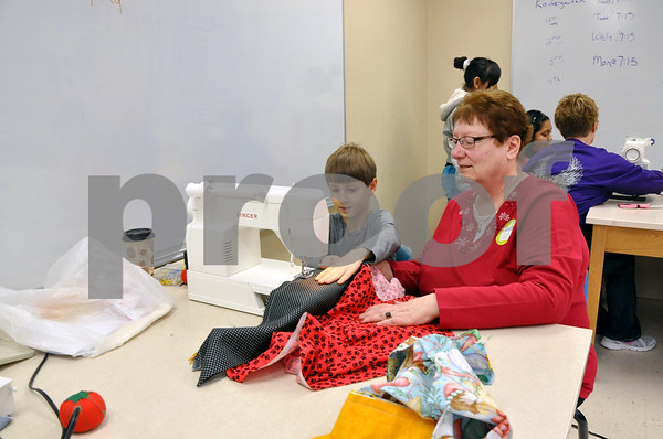 -Messenger photo by Joe Sutter<br /> <br /> Adam Herrington, 5th grade, sews a pillowcase with help from volunteer Loretta Moon. Herrington has never really used a sewing machine before. Moon said she's helped out with the event for several years. One year she couldn't come, and so cut up 350 fabric pieces for the kids to put together. The pillowcases were one of Aaron Eilerts' well-known projects. He used to buy the fabric himself and create the cases for children at the local hospital.