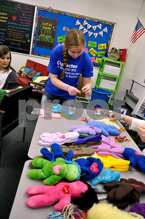-Messenger photo by Joe Sutter<br /> <br /> Freshman Sarah Wilson works on the doll project she helped organize. Wilson cut out doll patterns and sewed them, and the middle schoolers stuffed them during the Aaron Eilerts service day. The dolls will be sent to an orphanage in Haiti.
