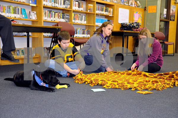 -Messenger photo by Joe Sutter<br /> <br /> Fifth-graders Shawn Mrazek, Megan Sampson and Maddie Anderson tie the fringes on a dog blanket, while Clover watches. Clover is a puppy in the Leader Dogs program in the Fort Dodge Correctional Facility, and is being sponsored by Eagle Grove high schoolers. The blankets made will be sent to the Leader Dog program.