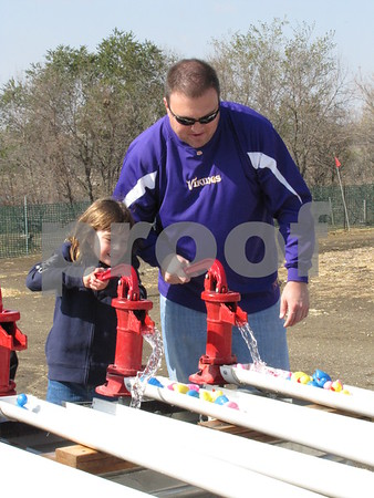 Madison and her dad, Jeff Pommer enjoy a little friendly competition at the water pumps at the 'Back 40 Playground' at Applefest.