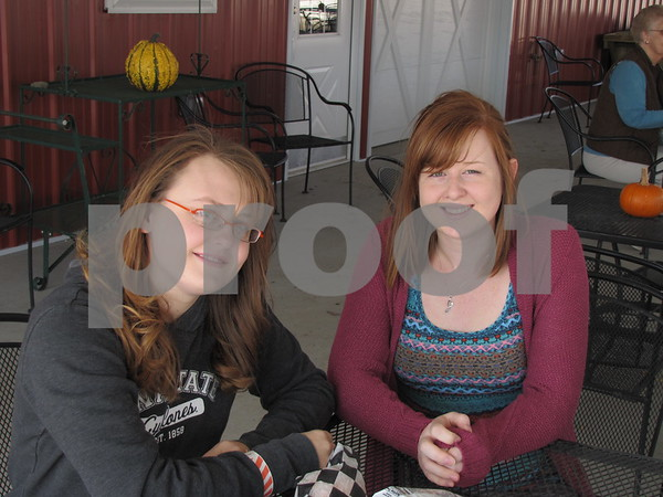 Sarah Trask and Kayla Treloar enjoy a snack under the canopy at the 'Back 40 Playground' at the Community Orchard.