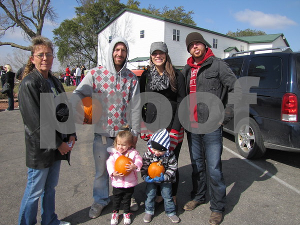 Robin Ewing, Dustin Ewing, Lindsey and Jerod George, and Chloey Ewing and Lincoln George hold the pumpkins they found in the pumpkin patch at the Community Orchard's Applefest.