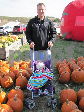 Tanner Lawrence with his daughter Ella stroll through one of the pumpkin patches at the Community Orchard during Applefest.