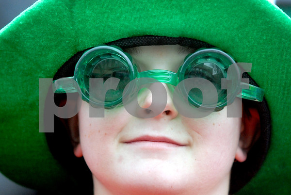 -Messenger photo by Hans Madsen<br /> <br /> Braeden Bennett, 13, of Emmetsburg, shows off the latest in green bottle goggles and hats Saturday afternoon while riding with the Palo Alto Relay for Life float in the annual St. Patrick's Day Parade.