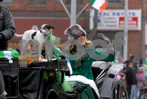 -Messenger photo by Hans Madsen<br /> <br /> Visiting Irish dignitary Deputy Michelle Mulherin, waves to the crowd during the annual St. Patrick's Day Parade in Emmetsburg. Mulhering is a member of the Irish Parliament. Dottie the dog, at left, keeps an eye out for Blarney.