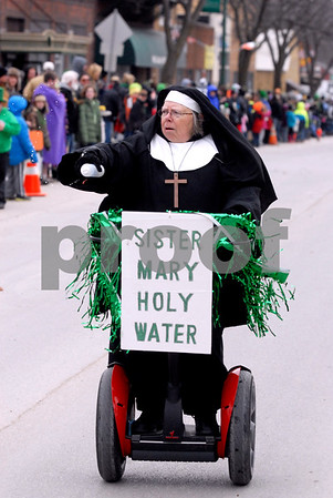 -Messenger photo by Hans Madsen<br /> <br /> Elaine Nauss, of Emmetsburg, zips along the parade route Saturday afternoon spraying water as her character Sister Mary Holy Water during the annual St. Patrick's Day Parade in Emmetsburg.