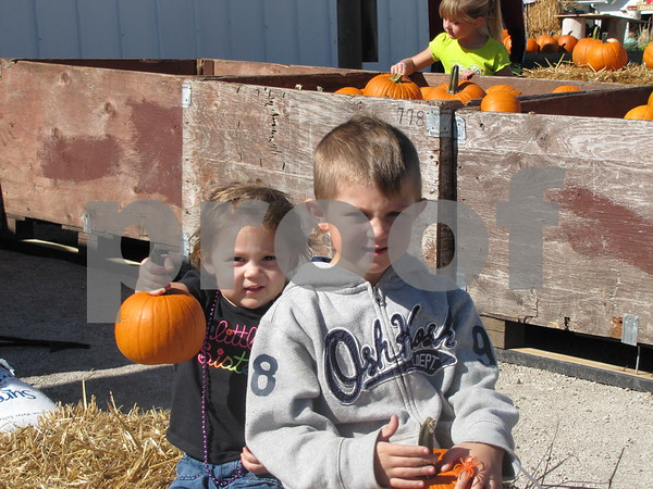 Caleigh and Tavian McClellan show the pumpkins they won at ring toss.