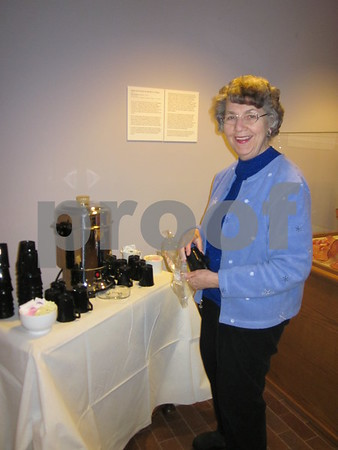 Blanden volunteer Mary Casey prepares for the crowd that will gather in the lobby after the Hans Madsen artist talk.