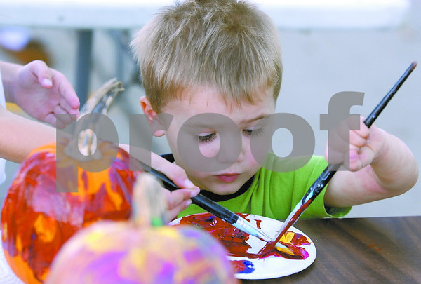 -Messenger photo by Hans Madsen<br /> <br /> Hudson Dutcher, 2, looks a bit surprised as his sister Sophia Dutcher, 6, reaches her brush in to collect some paint from the palette they were sharing at the pumkin painting event.