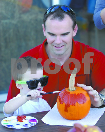 -Messenger photo by Hans Madsen<br /> <br /> Joe Kavanaugh, of Fort Dodge, watches as his son, Ronan Kavanaugh, 2, works on painting a pumpkin to take home Thursday afternoon during the Blanden Outreach Event at Graham Tire.
