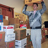 Colten Hill, a freshman at Fontbonne University and a member of the men's basketball team, carries boxes of books to be sent to Belize as part of the university's Books for Belize initiative.